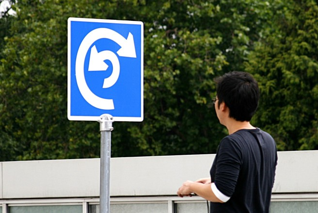 Man looking at confusing sign