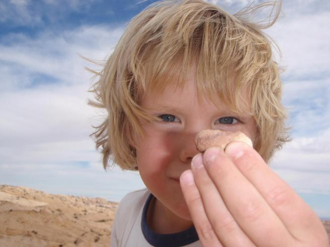 Boy stares at pebble, the power of attention